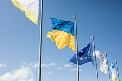 Ukraine and european union flags on flagpoles on sky background. Ukraine and european union flags on flagpoles Stock Images