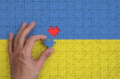 Ukraine flag is depicted on a puzzle, which the man`s hand completes to fold.  stock illustration