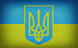 Ukraine flag. Grunge Ukrainian flag with trident on fabric backround Stock Photos