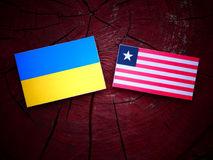 Ukraine flag with Liberian flag on a tree stump isolated. Ukraine flag with Liberian flag on a tree stump Royalty Free Stock Images