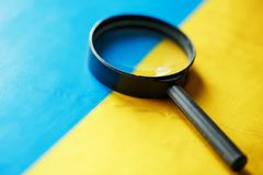 UKRAINE flag looking through a magnifying glass. The study of the history and culture of the people of the country of Ukraine. The. Concept of studying the royalty free stock images