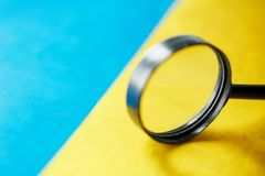 UKRAINE flag looking through a magnifying glass. The study of the history and culture of the people of the country of Ukraine. The. Concept of studying the stock photo
