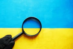 UKRAINE flag looking through a magnifying glass. The study of the history and culture of the people of the country of Ukraine. The. Concept of studying the stock photography