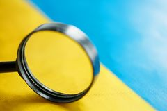 UKRAINE flag looking through a magnifying glass. The study of the history and culture of the people of the country of Ukraine. The. Concept of studying the royalty free stock photos