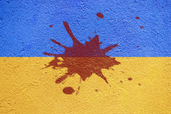 Ukraine flag painted on old concrete wall with blood blot Stock Photography
