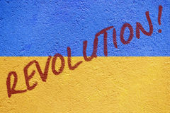 Ukraine flag painted on old concrete wall with REVOLUTION inscri Stock Image
