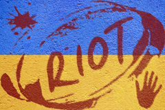 Ukraine flag painted on old concrete wall with RIOT inscription Royalty Free Stock Photos