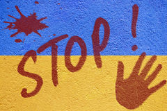 Ukraine flag painted on old concrete wall with STOP inscription Royalty Free Stock Image