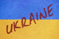 Ukraine flag painted on old concrete wall with UKRAINE inscripti Stock Images