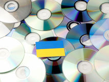 Ukraine flag on top of CD and DVD pile isolated on white. Ukraine flag on top of CD and DVD pile isolated Stock Images