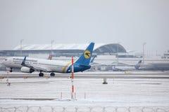 Ukraine International Airlines Boeing 737-800 UR-PSY, Schnee auf Rollbahn, München Lizenzfreie Stockbilder