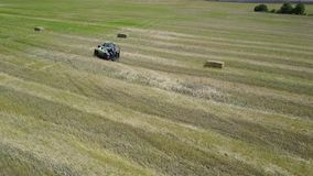 Ukraine, Kalinovka, September 4, 2017, Green tractor with Hay baler producing hay bales in a field - Aerial footage stock video footage
