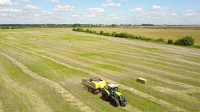 Ukraine, Kalinovka, September 4, 2017, Green tractor with Hay baler producing hay bales in a field - Aerial footage stock footage
