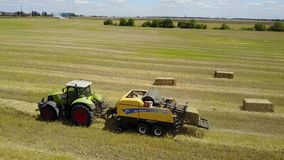 Ukraine, Kalinovka, September 4, 2017, Green tractor with Hay baler producing hay bales in a field - Aerial footage stock video