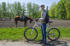 Ukraine, Kiev, April 29, 2018.Teenager boy with a bicycle on the background of a girl riding a horse