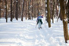 Ukraine, Kiev, City Forest in March, 2018. Active rest of retiree woman.Active middle aged woman skiing through winter forest. Full length of enthusiastic middle stock image