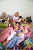 Ukraine, Kiev. A little girl among the dolls. A little girl among the dolls. Child on the couch among the children`s dolls royalty free stock photo