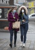 Ukraine Kiev March 23, 2020: Two young girls on Kiev street wearing medical mask for protection against coronavirus SARS-CoV-2 or