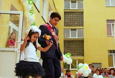Ukraine Kiev May 2019. Last call. Graduate and first-grader carry a big bell. Leading graduation line. Beautiful school with balls