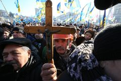 The miner in a helmet with a crucifix in his hand. Ukraine, Kiev. The miner in a helmet with a crucifix in his hand. Rally on the Maidan royalty free stock photo