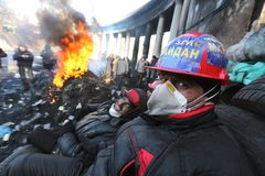 Ukraine. Kiev. Revolutionaries in helmets and masks near flaming tires. Ukraine. Kiev.near flaming tires. Rebels with a black face from soot. Riots in Kiev royalty free stock photo