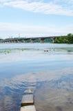 Ukraine, Kiev, Paton bridge over Dnipro river. With stones, water and algae on foreground Stock Photos