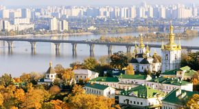 Ukraine. Kiev. Pechersk Lavra Church on the background of the Dnieper River and modern urban buildings on an autumn day stock photography