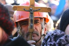 The miner at the rallies holds a crucifix in front of his face. Ukraine, Kiev. Protests against the authorities in the square Maidan. The miner at the rallies royalty free stock photo