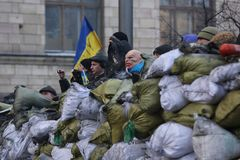 Revolutionary on the barricade with the flag. Ukraine, Kiev. A revolutionary on a barricade with a flag. a rebel in a mask of the devil on a barricade of bags royalty free stock photos