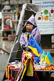 Ukraine, Kiev. The seller of souvenirs. Ukraine, Kiev. A girl in a cloak on the street Khreshchatyk sells European flags and souvenirs royalty free stock images