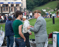 UKRAINE, KIEV - September 11,2013: Elderly man on the Independence Square earns a pretext to passersby know your weight and. Muscle power stock photo