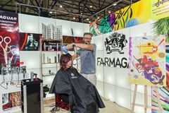 Hairdresser works with a model at the exhibition Stock Photos