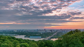 Ukraine. Kiev. Sunrise on the left bank of the. Ukraine. Kiev. Beautiful Sunrise in clouds on the left bank of the Dnieper River timelapse with bridge and green stock video