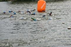 UKRAINE, LEMBERG - SEPTEMBER 2018: Athletenschwimmer schwimmen entlang dem See in den Wetsuits während des Triathlonwettbewerbs stockfotos