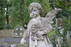 Ukraine, Lviv, Lychakivskiy Cemetery-September 26, 2011: Stone monument statue in the shape of an angel with flowers. In a cemetery in the autumn afternoon Royalty Free Stock Photo