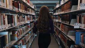 Ukraine, Lviv - March 26, 2018: Girl with long hair walks along the shelves in the library. Concept: educational stock video