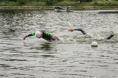 UKRAINE, LVIV - SEPTEMBER 2018: Athletes swimmers swim along the lake in wetsuits during the triathlon competition. Athletes swimmers swim along the lake in Stock Photo