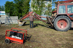 UKRAINE - MAY 06, 2017: The electric welder repairs the excavator by welding. Diesel generator for emergency electric power. Royalty Free Stock Photos