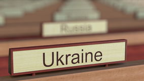 Ukraine name sign among different countries plaques at international organization. 3D rendering Stock Photos