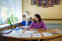 Ukraine, Odessa 2. August 2017 Frau im Büro am Tisch sekretärin Medizinische Arbeitskraft lizenzfreie stockfotografie