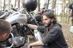 UKRAINE,PIROGOVKA - APRIL 28,2018: A young man, biker repairing a motorcycle in the forest near the village Pirogovka. royalty free stock image