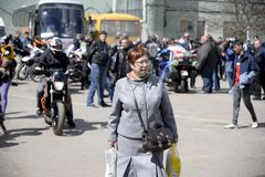 UKRAINE,SHOSTKA - APRIL 28,2018: Senior woman walking near a motorcycle rally in the Shostka City Park. UKRAINE,SHOSTKA - APRIL 28,2018: Senior woman in a Royalty Free Stock Images