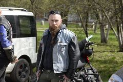 UKRAINE,SHOSTKA - APRIL 28,2018: A young man biker with a beard and in denim waistcoat in the Shostka City Park. UKRAINE,SHOSTKA - APRIL 28,2018: A young Royalty Free Stock Photography
