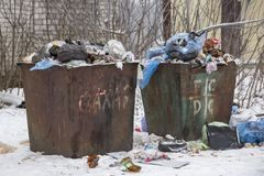 UKRAINE, SHOSTKA - December 21, 2018: Two old, dirty trash bins with scattered garbage near them royalty free stock photos