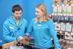 Ukraine, Shostka -March 8, 2019: Sellers consultants stands behind the store counter stock photography