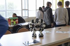 UKRAINE,SHOSTKA-MAY 12,2018: Schoolchildren look at the robot at the exhibition in IT Center. UKRAINE,SHOSTKA-MAY 12,2018: Schoolchildren look at the robot with Stock Images