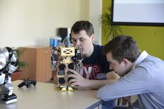 UKRAINE,SHOSTKA-MAY 12,2018: Schoolchildren look at the robot at the exhibition in IT Center. UKRAINE,SHOSTKA-MAY 12,2018: Schoolchildren look at the robot with Royalty Free Stock Photography
