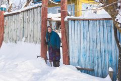 Ukraine, Svirzh, St. Lesnaya - January 13, 2019: Old grandmother stands near her house in the village in winter royalty free stock photos