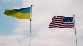 Ukraine and United States flags fluttering in wind. With bright sky in background stock footage