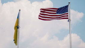 Ukraine and United States flags fluttering in wind stock video
